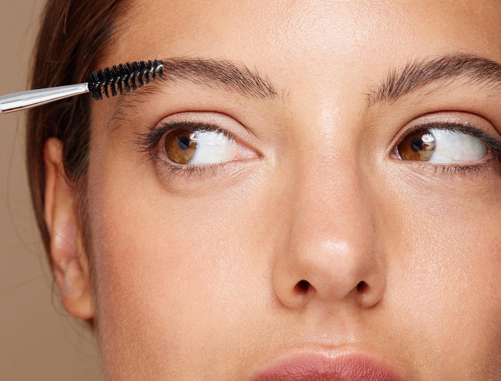 woman grooming her eyebrows