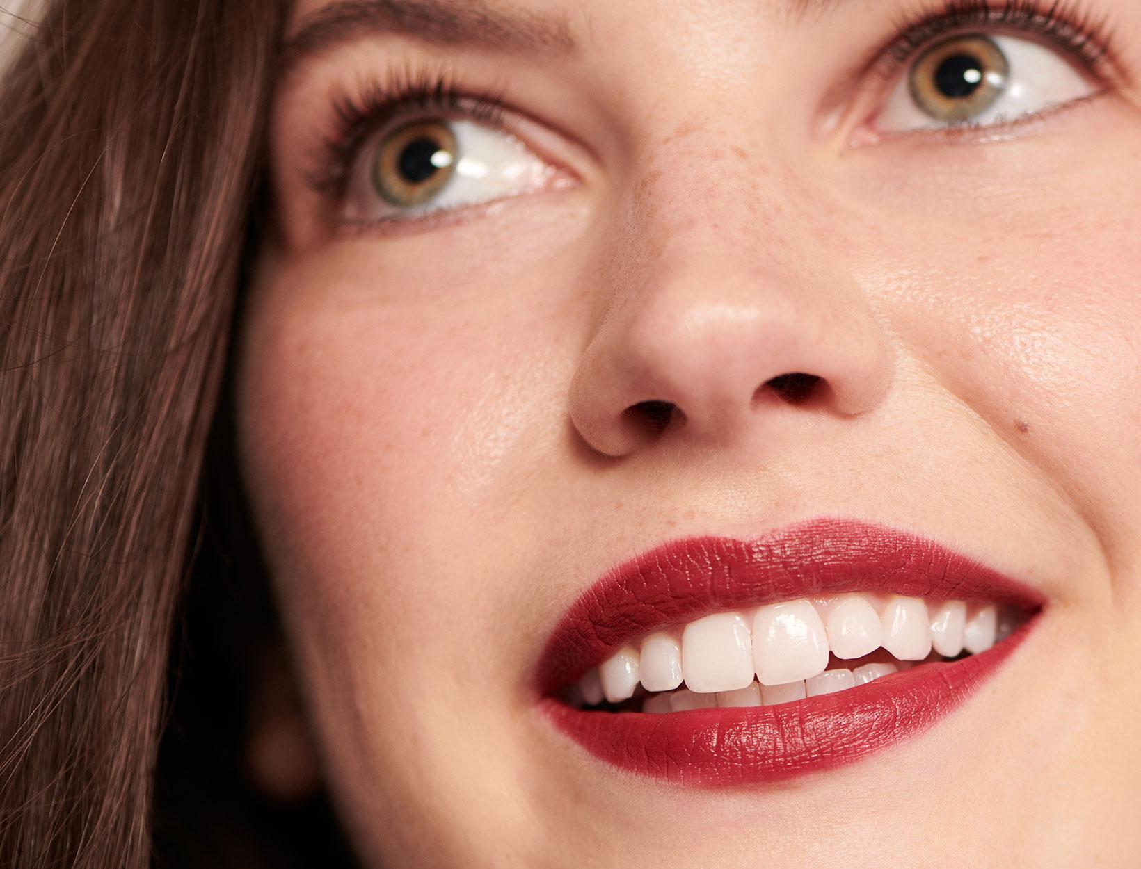Model smiling wearing red lipstick