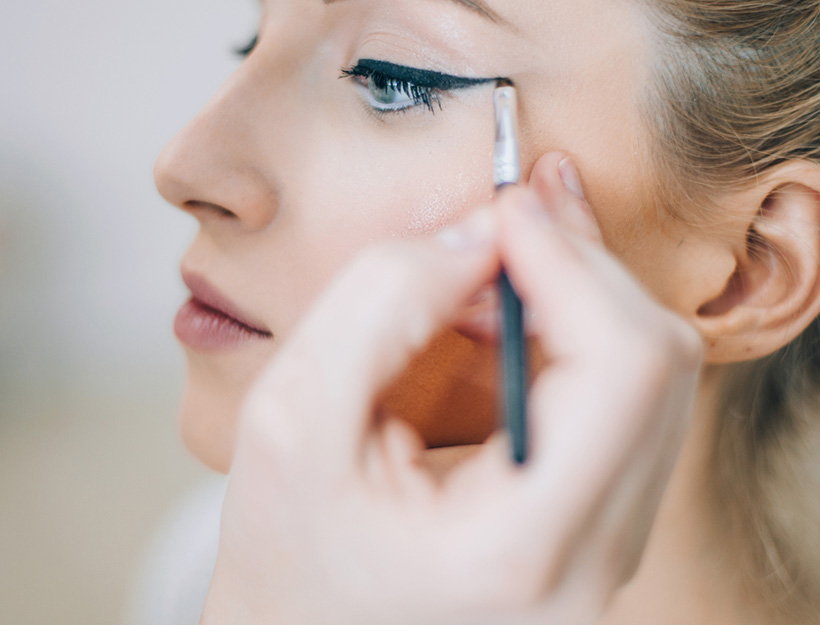 Woman putting on eyeliner