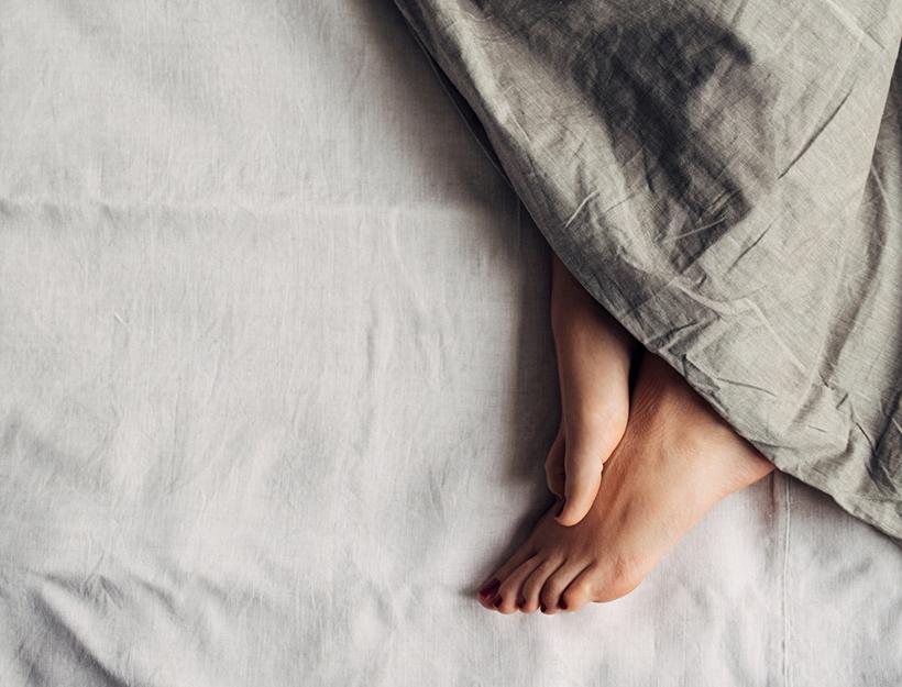 Feet of a woman sleeping under a comforter.