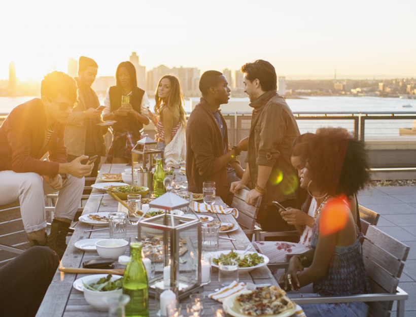 Friends enjoying rooftop party --- Image by © Boone Rodriguez/Corbis