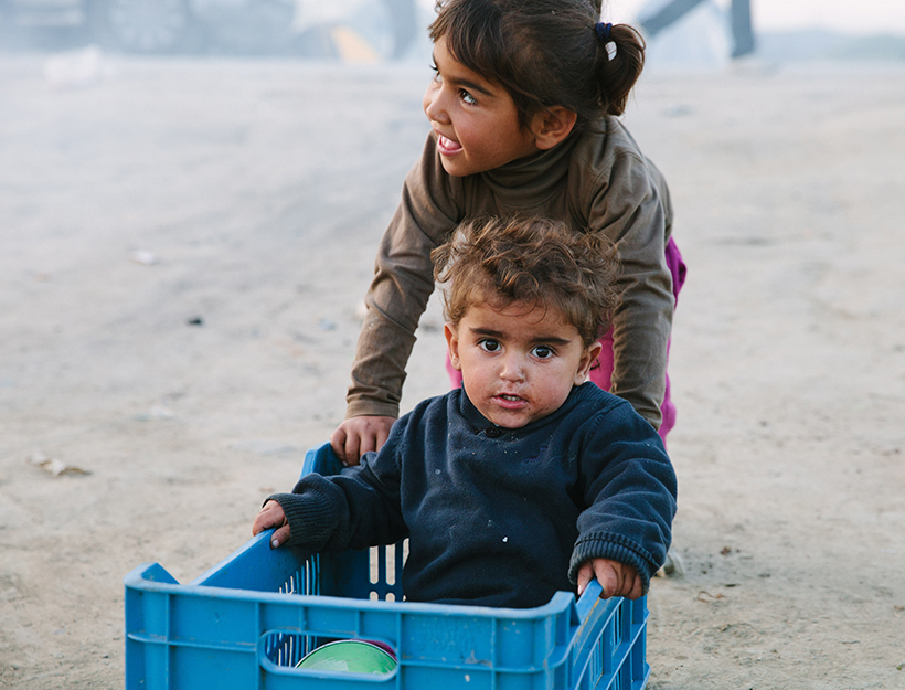 Mandatory Credit: Photo by Kit Oates/REX/Shutterstock (5621249n) Two Syrian children play in a plastic box outside their tent in Idomeni, they have been waiting to cros the border for a month, but are being sent back to Turkey by the EU Migrant crisis at Idomeni refugee camp, Greece - 24 Mar 2016