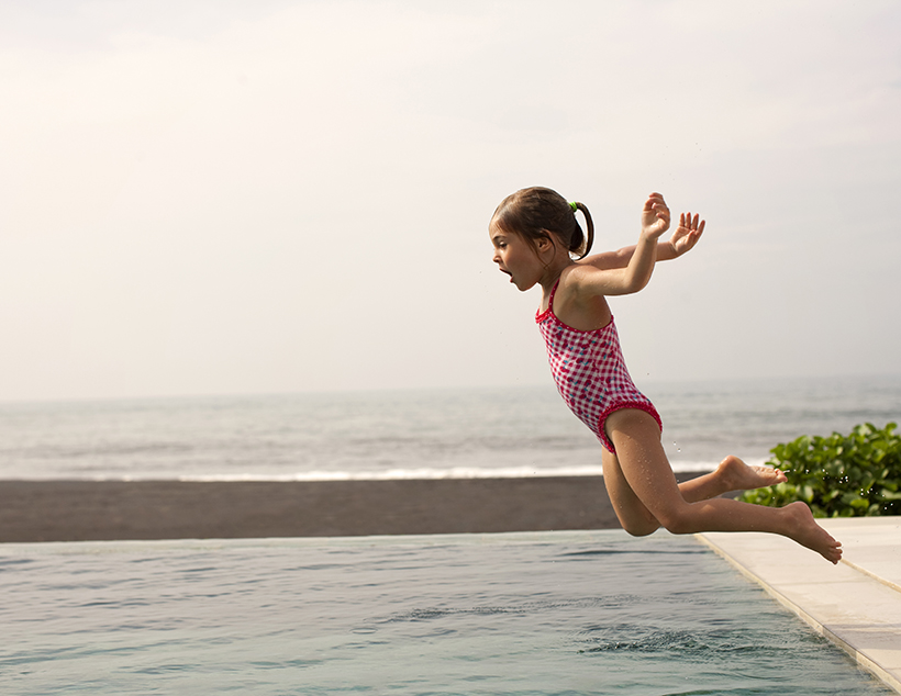 A young girl goofily jumps into a pool.