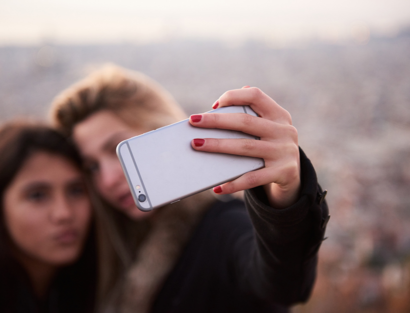 Two young women sticking out tongues while taking selfie. Bokeh.