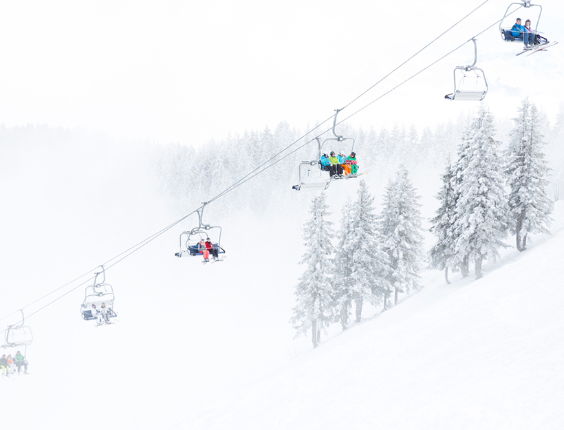 A ski lift gliding up a snowy misty ski slope with snow covered trees.