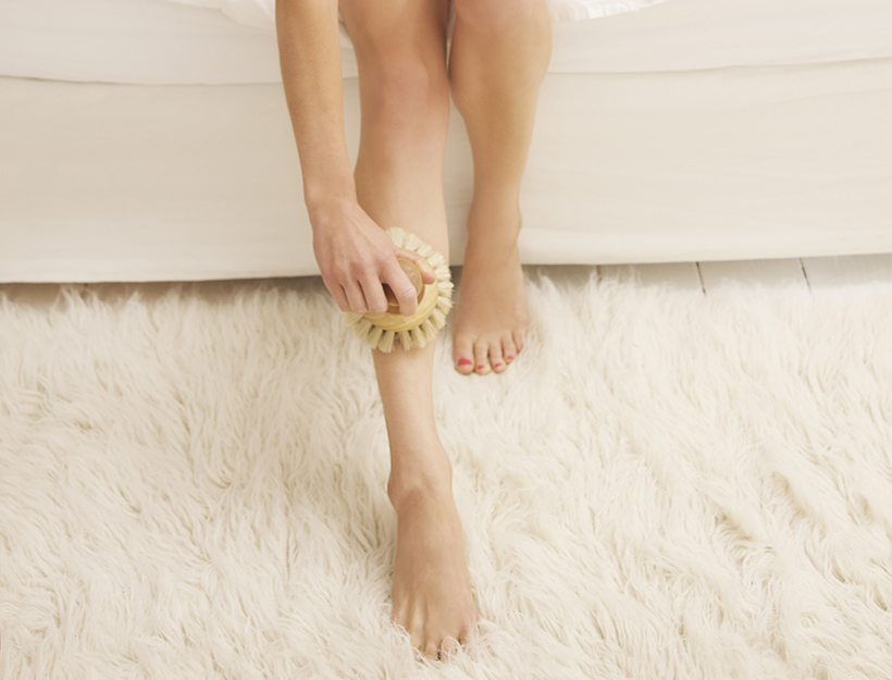 Woman Sitting on Bed Exfoliating her Leg