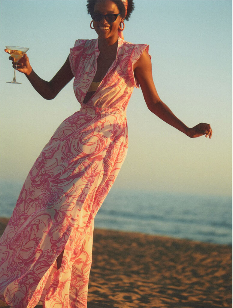 Model dancing on the beach with martini