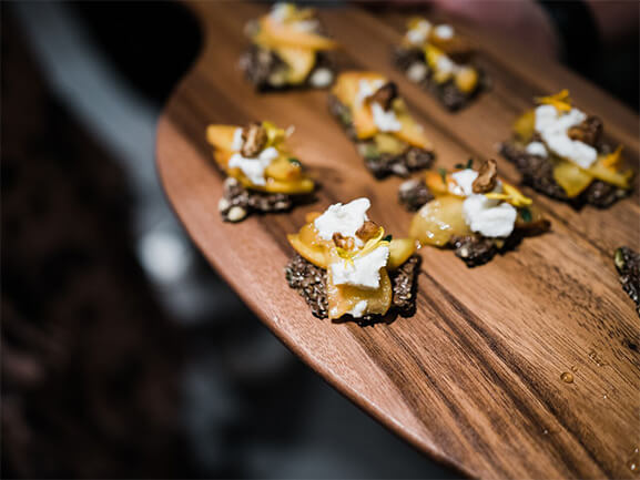 Chef's genius: Peaches, walnuts, honey, and ricotta on flax & pepita crisps.