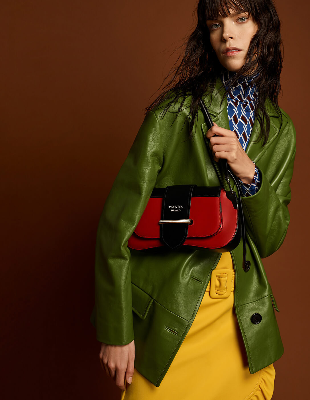 Prada model with red bag and green coat