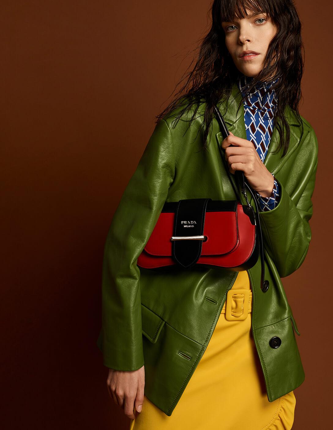 Prada model with red bag and green coat