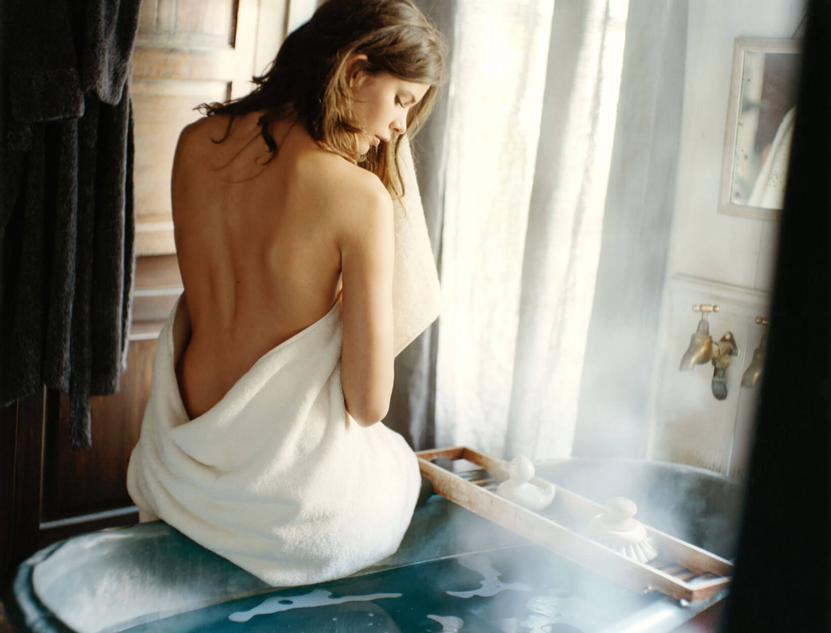 a woman in a towel sitting on the edge of a bathtub