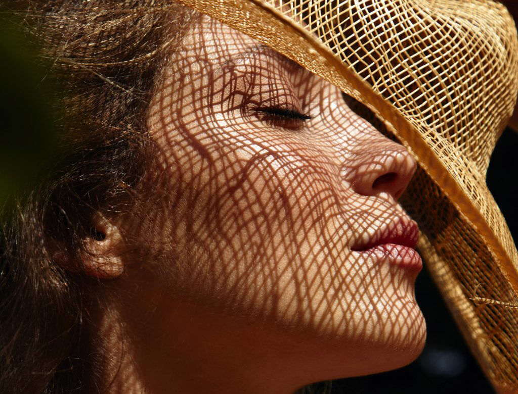 close up shot of woman in a straw hat closing her eyes