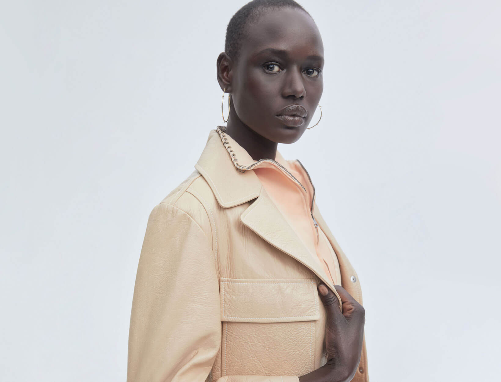 a model in a tan jacket