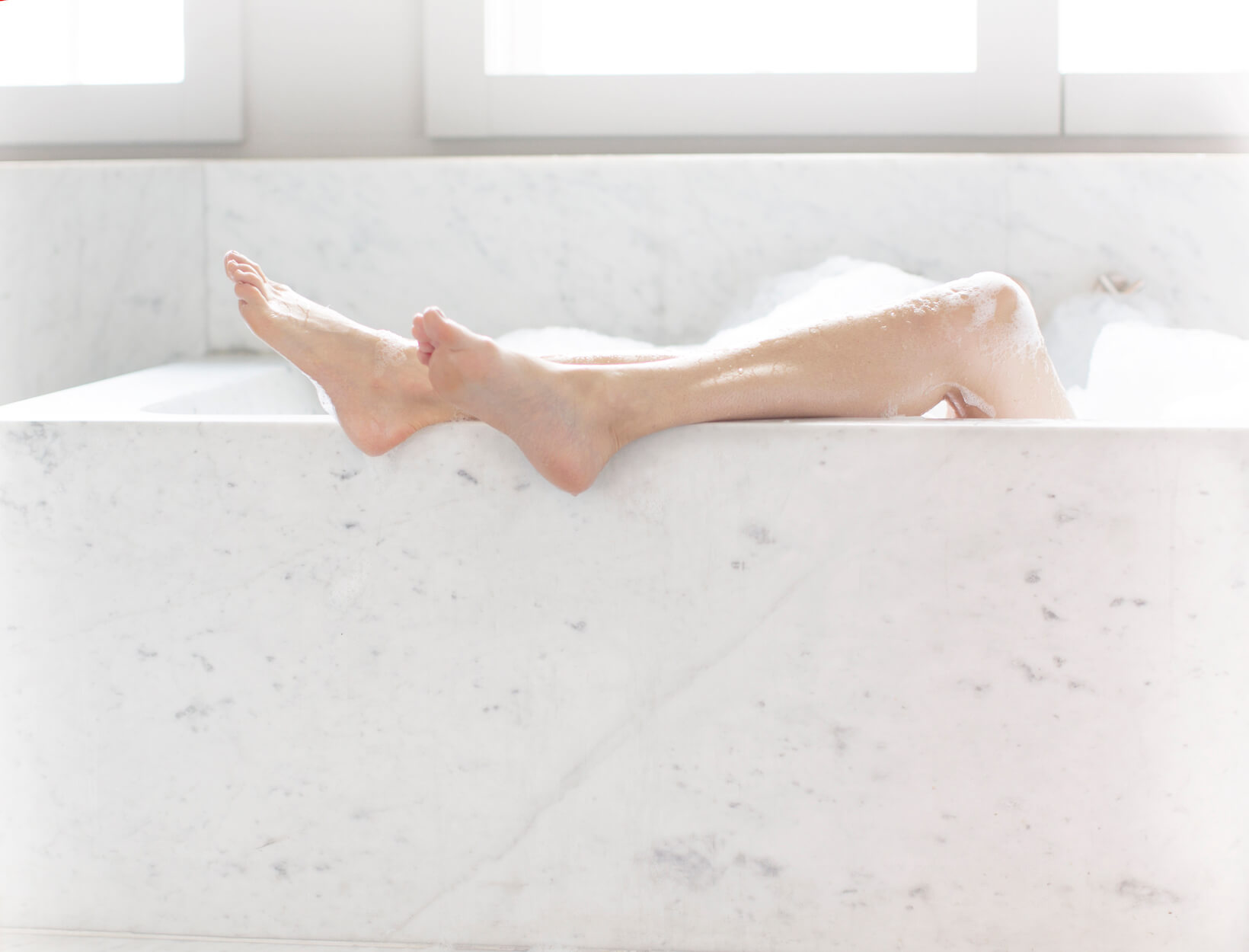 feet hanging out of a bathtub