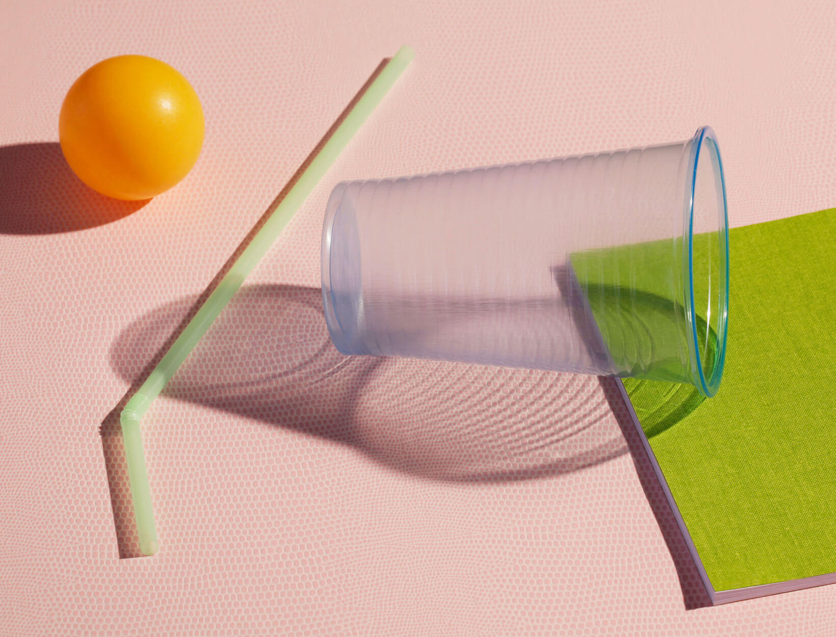 photo of a ping pong ball, plastic straw, and a plastic cup