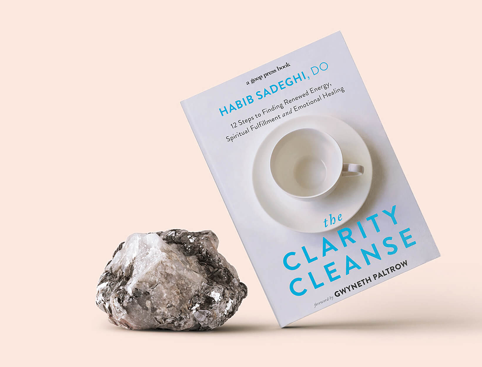 The Clarity Cleanse book standing on the bottom left corner next to a silver colored mineral rock