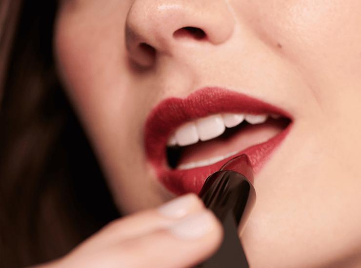 Model putting on dark red lipstick