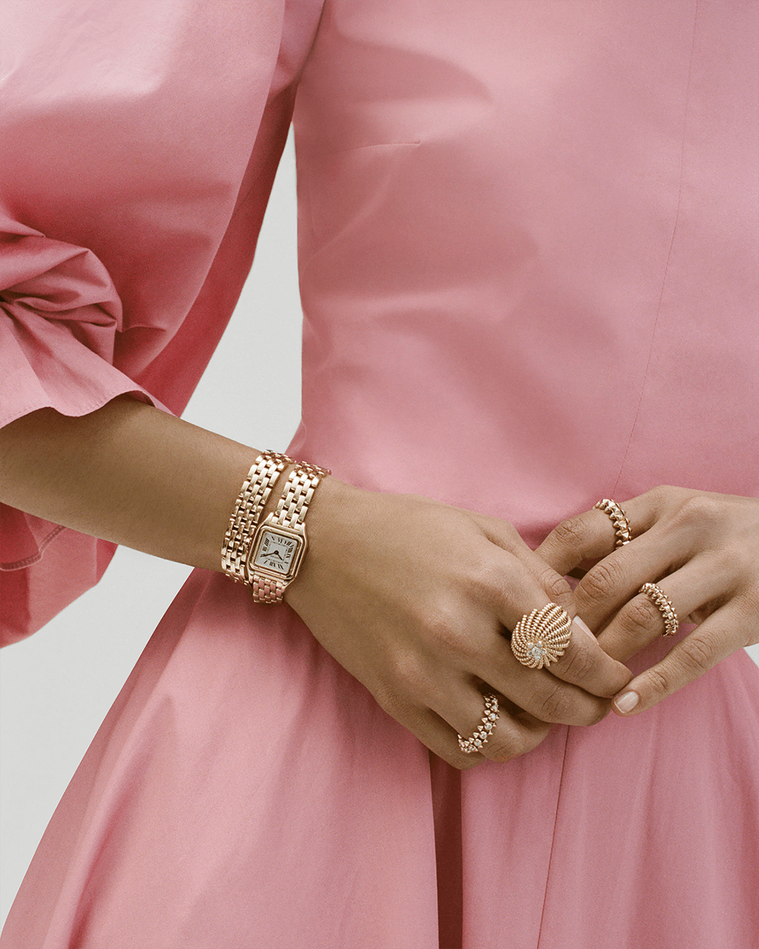 woman with roskanda dress and cactus ring in yellow gold with yellow gold watch and pink gold rings also with diamonds