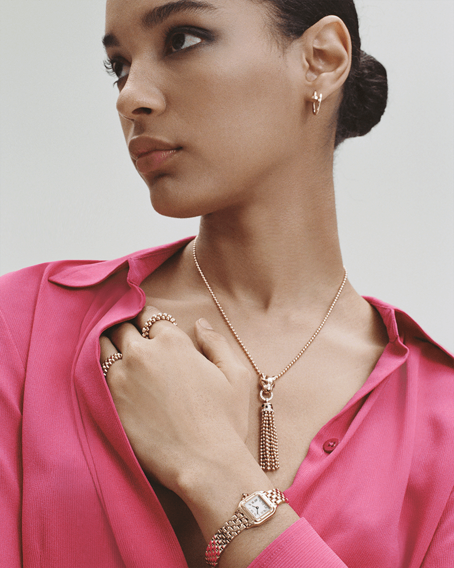woman in pink dress with necklace pink gold rings, yellow gold watch and earrings