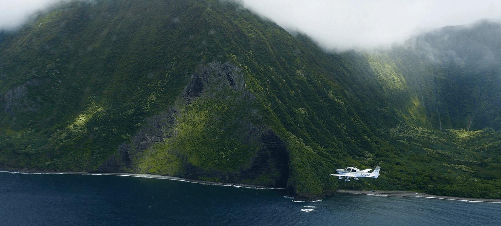 plane flying along coastline
