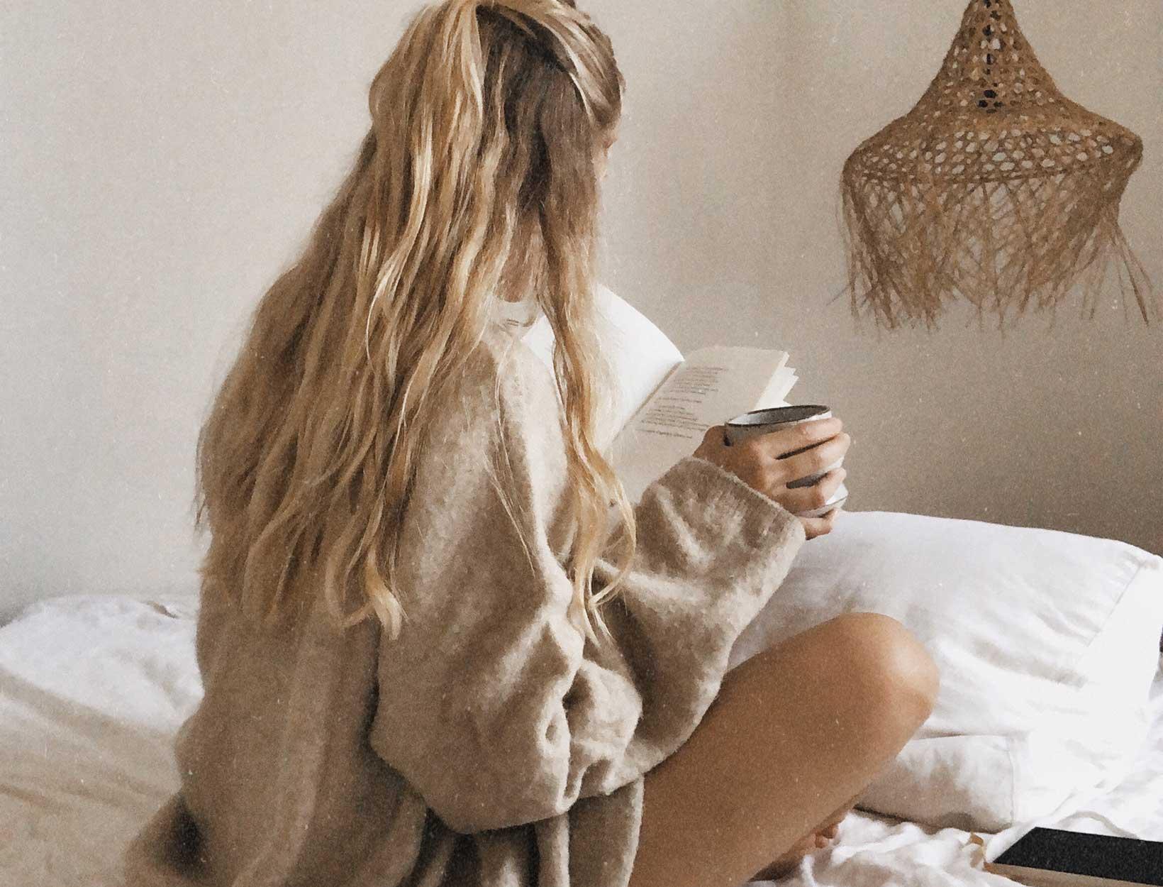 woman in sweater reading