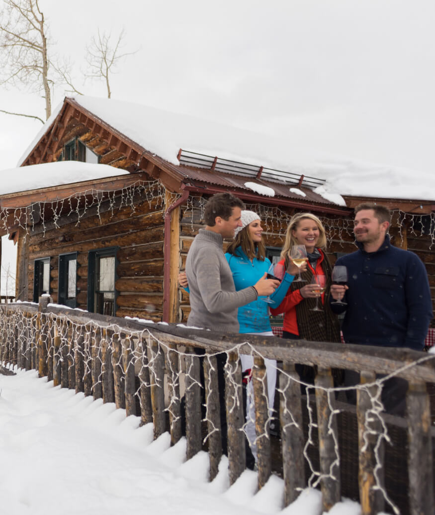 people smiling outside of a cabin