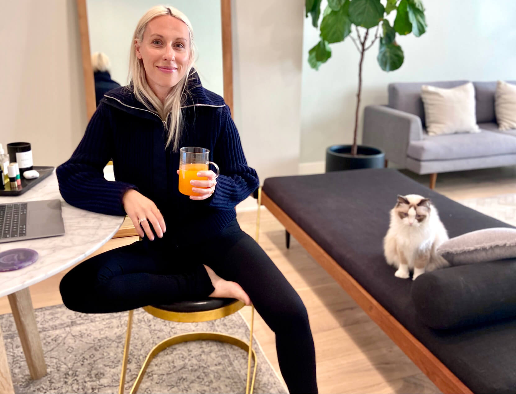 ali pew holding a glass of juice