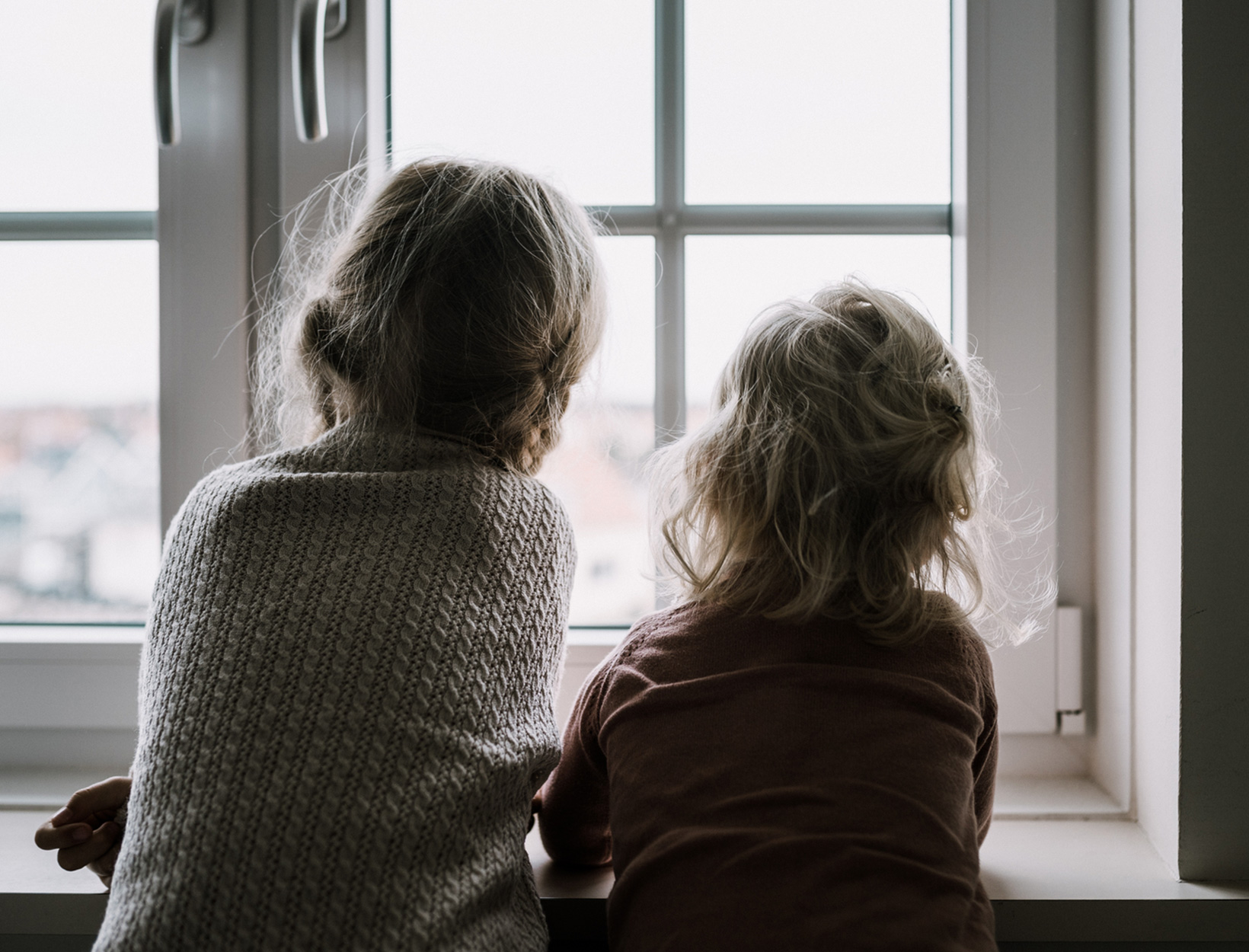 two children looking out window