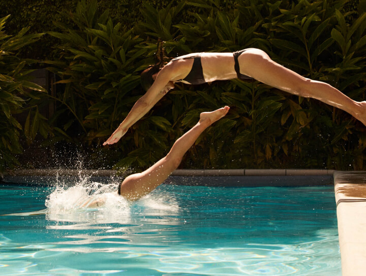 women diving into a pool
