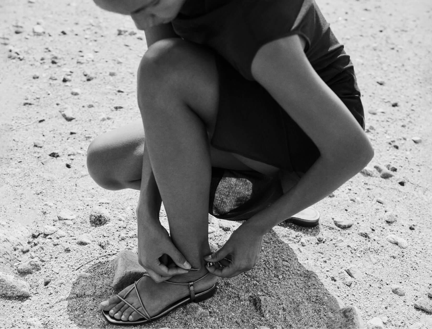 woman on beach adjusting sandals