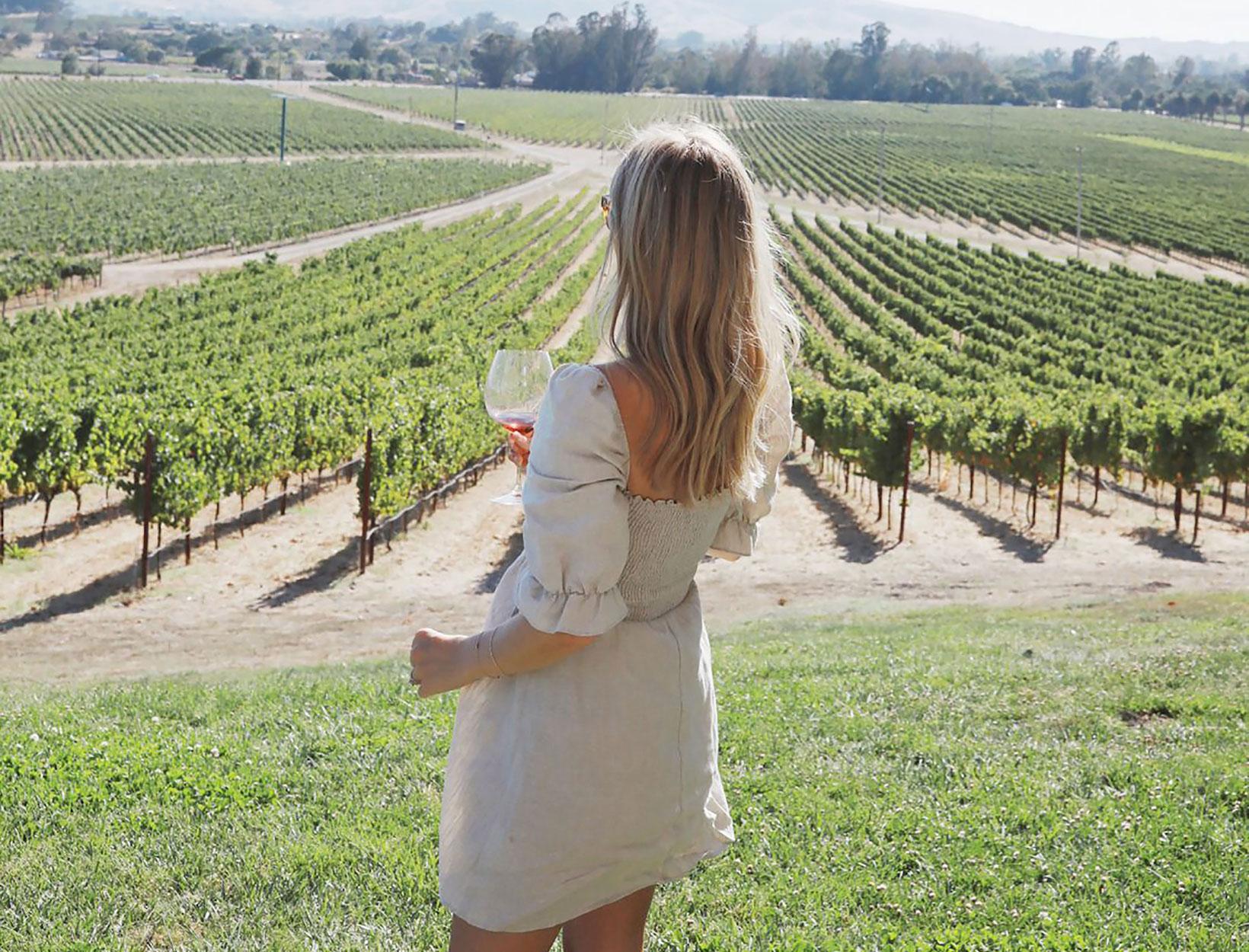 woman in a sundress drinking wine outside