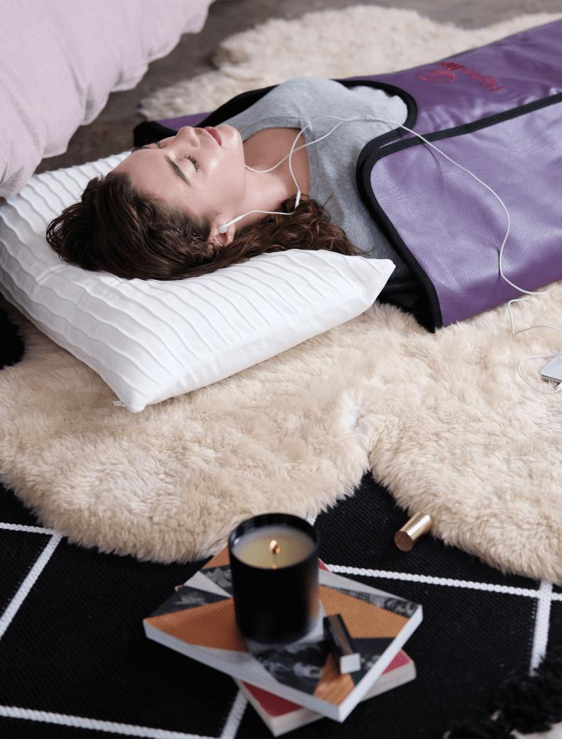 woman using an infrared sauna blanket