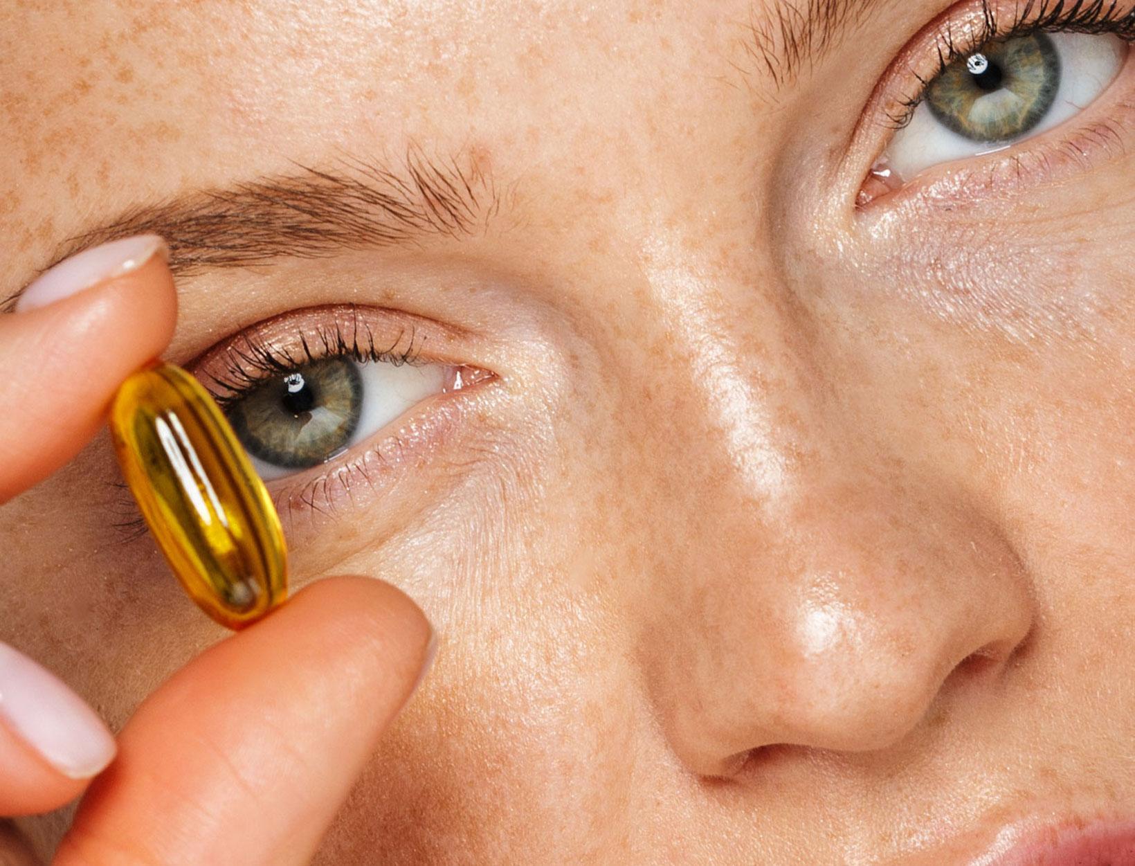 woman holding a supplement pill
